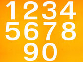 Close up on white stenciled number on yellow wall — Stock Photo