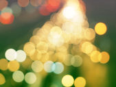 Yellow christmas background with bokeh lights — Stock Photo