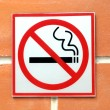Stock Photo: Sign hangs on brick wall warning that smoking is not permitted in area