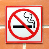 Sign hangs on a brick wall warning that smoking is not permitted in the area — Stock Photo