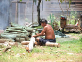 RAYONG, THAILAND - AUGUST 13: Unidentified man cuts woods to make charcoal on August 13, 2012 in Rayong, Thailand. — Stock Photo