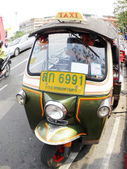 BANGKOK - JANUARY 4: Tuk-tuk moto taxi on the street in the Wat suthat area on January 4, 2012 in Bangkok. Famous bangkok moto-taxi called tuk-tuk is a landmark of the city and popular transport — Foto Stock