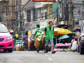 BANGKOK,THAILAND -SEPTEMBER 8: An unidentified worker pushes a cart full of vegetables through the vegetable market on September 8, 2012 in Bangkok, Thailand. — Stockfoto
