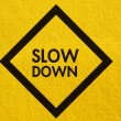 Slow Down yellow road sign painted on a stucco wall outside — Stock Photo #50484429