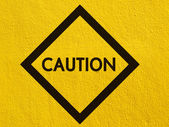 Caution traffic sign painted on a stucco wall outside — Stock Photo