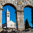 White Church Framed in the Arch of Ancient Roman Amphitheater in — Stock Photo #12246407