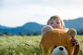 Girl and Teddy bear in a wheat field — Stock Photo
