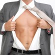 Fit for business - young businessman dressed in suit, shirt and tie pulling his shirt open revealing well-built torso - Stock Photo