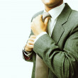 Young businessman fastening tie - Stock Photo