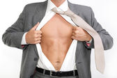 Fit for business - young businessman dressed in suit, shirt and tie pulling his shirt open revealing well-built torso — Stockfoto