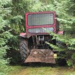 Stock Photo: Tractor left in the woods
