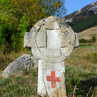Old cross with touristic sign - Stock Photo