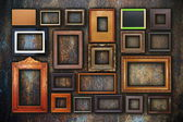 Grunge wall full of old frames — Stock Photo