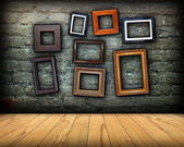 Scratched wall full of wood frames — Stock Photo