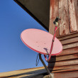 Stock Photo: Satellite dish attached to home.