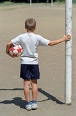 Boy with football, back view — Stock Photo