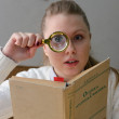 Woman reading a book with a magnifying glass — Stock Photo #15392781