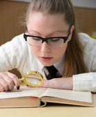 Woman reading a book with a magnifying glass — Stock Photo