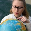 Woman examining a globe — Stock Photo