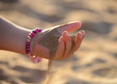 Sand pours out of the child hand — Stock Photo