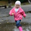 Girl jumping in puddles — Stock fotografie