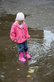 Girl standing in puddles — Stock Photo