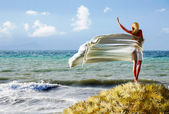 Woman with a tissue on a beach — Stockfoto