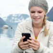 Young blond woman with her Smartphone in the hand — Stock Photo #13859196