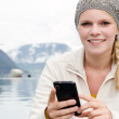 Young blond woman with her Smartphone in the hand — Stok fotoğraf