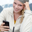 Young blond woman with her Smartphone in the hand — Stock Photo #13859252