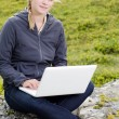 Foto de Stock  : Young blond womsits with laptop on stone