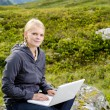 Young blond woman sits with a laptop on a stone — Стоковая фотография