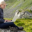 Stock Photo: Young blond woman sits with a laptop on a stone