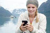 Young blond woman with her Smartphone in the hand — Stock Photo