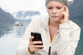 Have young blond woman with her Smartphone in the hand — Stok fotoğraf