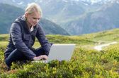 Jovem mulher loira senta-se com o laptop no prado alpino — Foto Stock