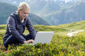 Young blonde woman sits with laptop in alpine meadow — Stok fotoğraf