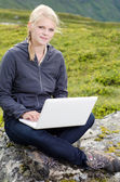 Young blond woman sits with a laptop on a stone — Stok fotoğraf