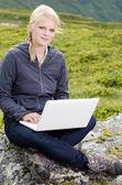 Jeune femme blonde se trouve avec un ordinateur portable sur une pierre — Photo