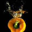 Orange pepper falls in the water — Stockfoto