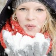 Young blond womblows in handful of snow — Foto de stock #22561803