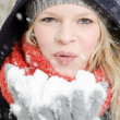 Young blond womblows in handful of snow — Stock Photo #22561803