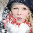 Young blond woman blows in a handful of snow — Lizenzfreies Foto