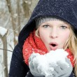 Young blond woman blows in a handful of snow — Foto de Stock