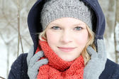 Young blond woman with beanie and scarf winter wood portrait — Stockfoto
