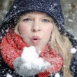 Young blond woman blows in a handful of snow — Стоковая фотография