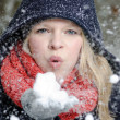 Young blond woman blows in a handful of snow — Foto Stock