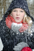 Young blond woman blows in a handful of snow — Stock Photo