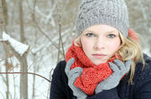 Young blond woman with beanie and scarf winter wood portrait — Стоковое фото