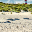 Lighthouse behind beach and dunes — Stok fotoğraf